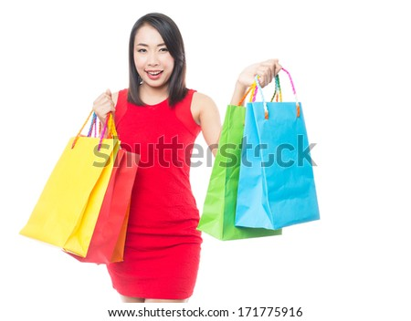 Young asian brunette woman with shopping bags on white background