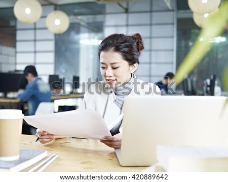 young asian business executive working in office looking at a report. - stock photo