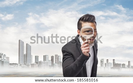young asian business man looking through a magnifying glass - stock photo