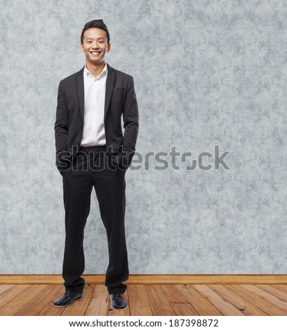 young asian business man smiling standing indoor - stock photo