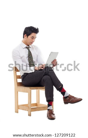 Young Asian business man using a pad PC sitting on the chair isolated on white background. - stock photo