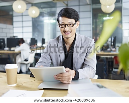 young asian business man working in office using tablet computer. - stock photo