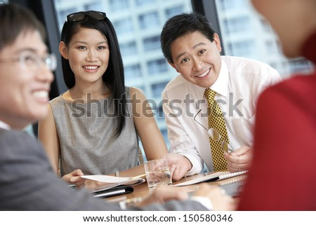 Young Asian business people having discussion in boardroom - stock photo