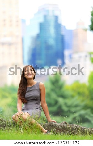 Young Asian Business woman in New York Central Park. Businesswoman looking up at copy space with skyscraper buildings from New York skyline in background. Young female professional. Mixed race. - stock photo