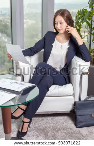 Young asian business woman suit looking stock photo for Sitting easy chairs