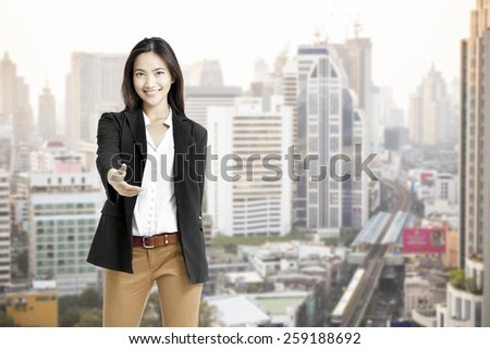 Young asian business woman in the big city,hand shake.