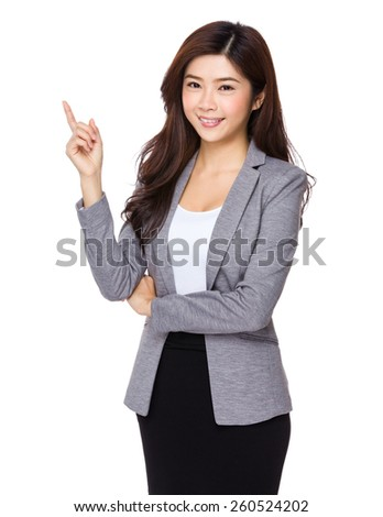 Young asian business woman pointing on copy space - stock photo