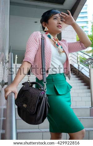 Young Asian business woman smiling, walking at an outdoor office environment