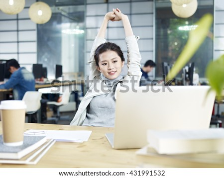 young asian business woman stretching upper body in office after task completed. - stock photo