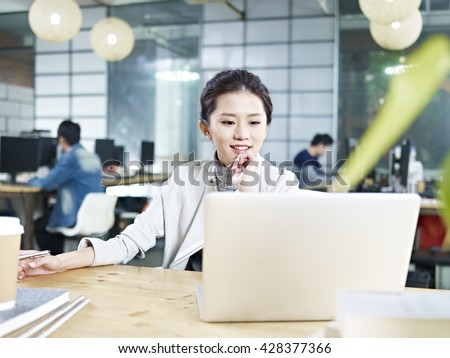 young asian business woman working in office using laptop computer. - stock photo