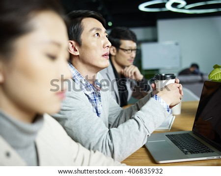 young asian businessman looking up and thinking during meeting in office. - stock photo