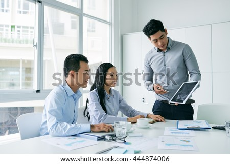 Young Asian businessman showing presentation on tablet computer to investors