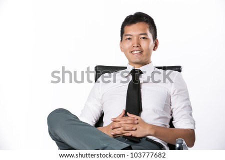 Young Asian businessman sitting back in his chair. Isolated on a white background. - stock photo