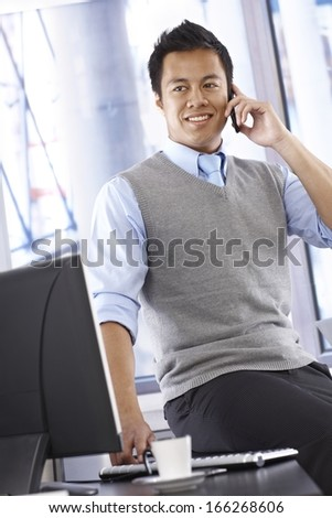 Young Asian businessman talking on mobilephone, smiling, looking away, sitting on top of desk. - stock photo