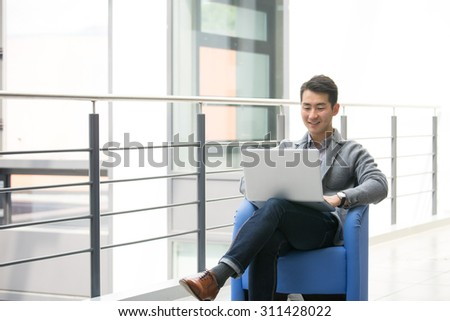 Young asian businessman using tablet, mobile phone in the office - stock photo