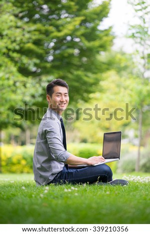 Young asian businessman using tablet, mobile phone in the park