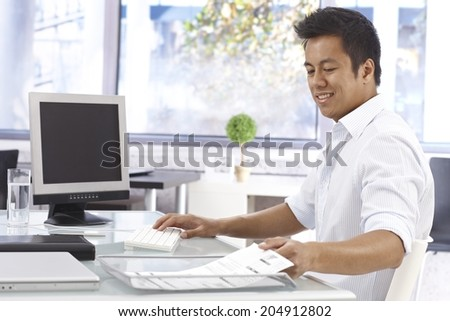 Young Asian businessman working in bright office, sitting at desk. - stock photo