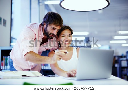 Young asian businesswoman getting advice from office colleague at her desk, couple of businesspeople deep in discussion before a laptop in a corporate lounge, students talking together over computer - stock photo