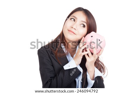 Young Asian businesswoman listen to piggy bank  isolated on white background - stock photo