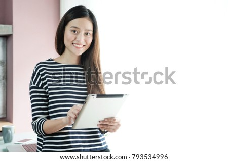 Young asian businesswoman using tablet with smiling face, positive emotion, at office, casual office life concept