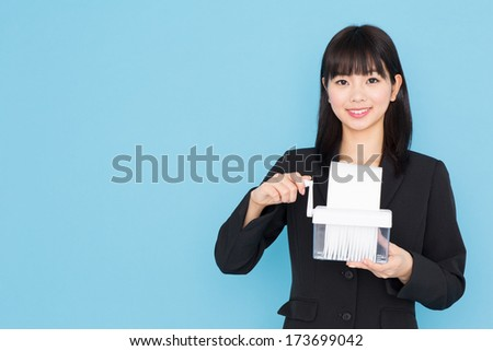 young asian businesswoman with shredder on blue background