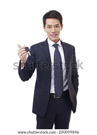 young asian car salesman holding car key, isolated on white. - stock photo