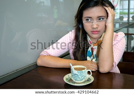 Young Asian college girl student sitting on campus cafe, feel depress - stock photo