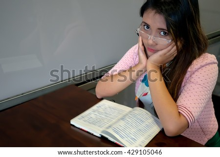 Young Asian college girl student sitting on campus cafe, thinking and writing notebook - stock photo