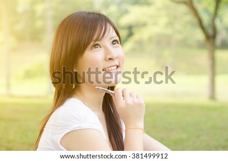 Young Asian college girl student sitting on campus lawn and thinking. - stock photo