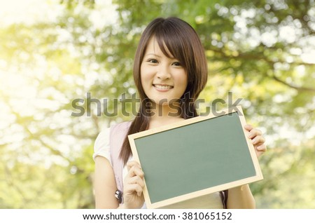 Young Asian college girl student standing on campus lawn, holding a blank chalkboard and smiling. - stock photo