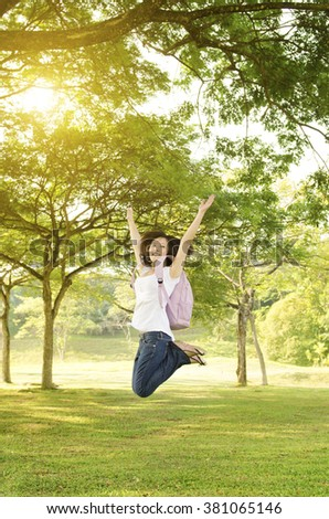 Young Asian college girl student standing on campus lawn, open arms jumping and smiling. - stock photo