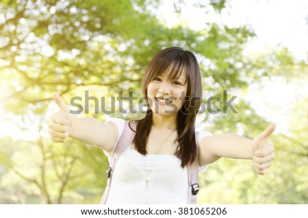 Young Asian college girl student standing on campus lawn, showing thumbs up and smiling. - stock photo