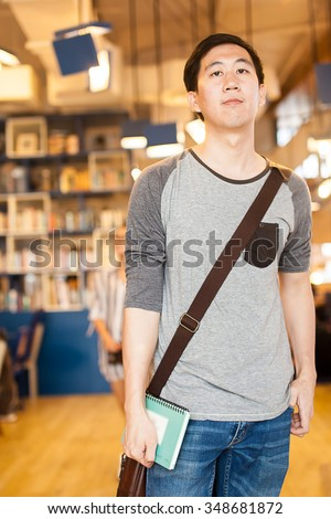 Young Asian college man standing in school library - stock photo