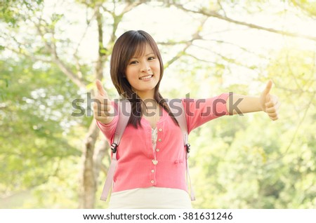 Young Asian college student on campus,  showing thumbs up. - stock photo