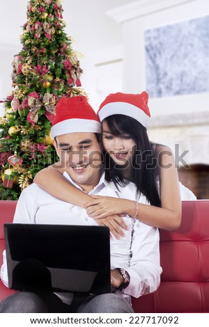 Young asian couple enjoy christmas holiday and buy online together with laptop