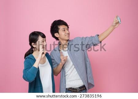 young asian couple enjoy their self-portrait. - stock photo