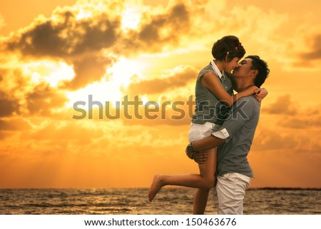 Young asian couple in love staying and kissing on the beach on sunset - stock photo