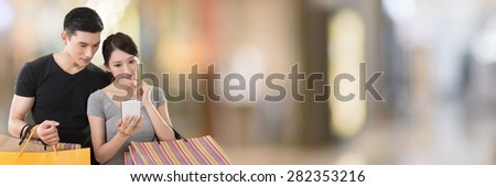 Young Asian couple shopping and looking at cellphone in the mall - stock photo
