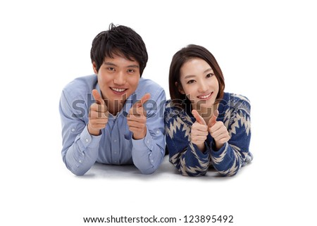 Young Asian couple showing thumbs