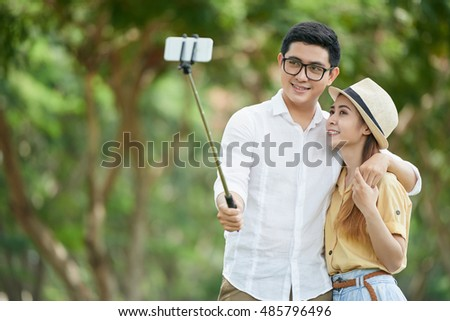 Young Asian couple taking selfie outdoors