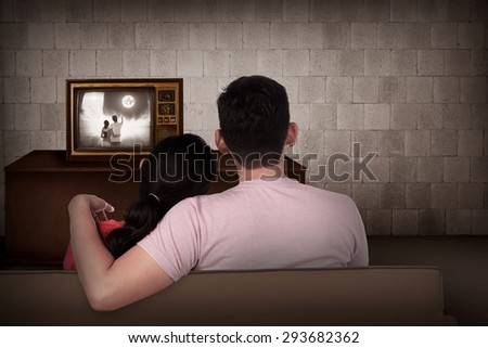 Young asian couple watching retro tv in the house - stock photo