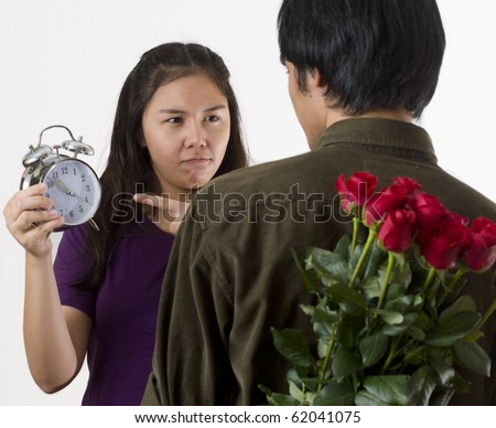 Young Asian couple with man holding flowers behind his back and woman pointing to clock indicating that He is late - stock photo