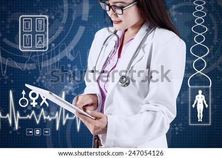 Young asian dentist working on tablet computer with futuristic medical background - stock photo