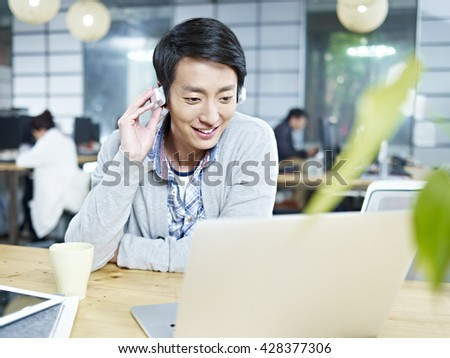 young asian designer looking at laptop computer while listening to music with headphones in office. - stock photo