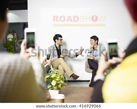 young asian entrepreneur being interviewed while the audience taking pictures using cellphone during roadshow. - stock photo