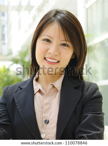 Young Asian executive standing outside office building - stock photo