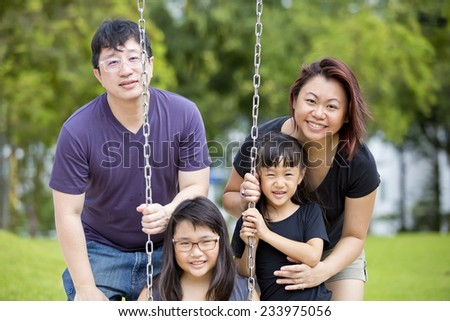 Young Asian family playing swing bonding in park - stock photo