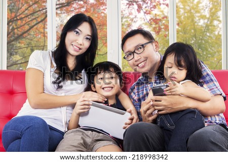 Young asian family smiling at camera while using digital tablet at home with autumn background on the window - stock photo