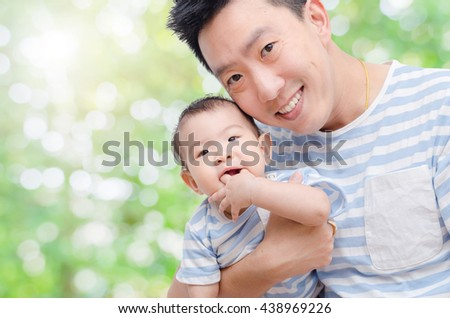 Young asian father with his child in garden