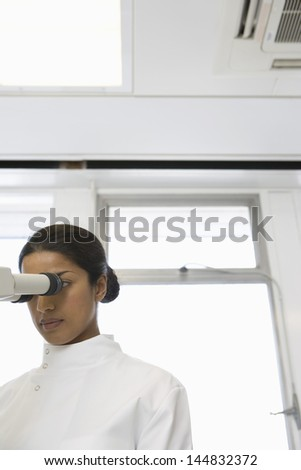 Young Asian female scientist using microscope in laboratory - stock photo